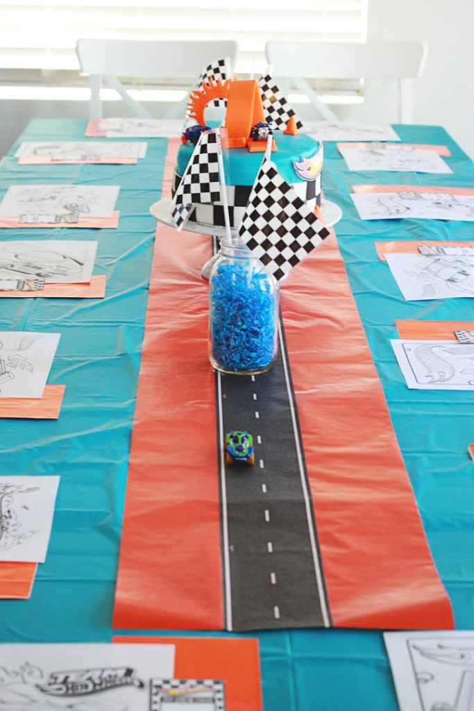 Hot Wheels birthday party table decorations with blue and orange color scheme and road table runner with cars and racing flags.