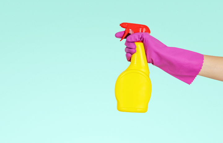 gloved hand holding spray bottle