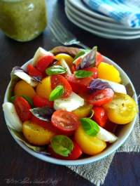 a gorgeous slightly modified version of a Caprese Salad that uses bright vine-ripened yellow Campari tomatoes, gorgeous red Roma tomatoes, and tiny grape tomatoes, fresh moist mozzarella cheese, green sweet basil, fresh purple basil, and genuine extra-virgin olive oil, seasoned simply with kosher salt and freshly ground pepper.