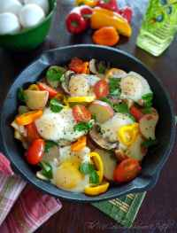 Italian Style Breakfast skillets are a hearty and delicious combination of red skinned potatoes, sunny side up eggs, onions, sweet mini peppers, baby Bella mushrooms, tomatoes, fresh spinach, and simply seasoned with Italian herbs, kosher salt, and freshly ground pepper all in one cast iron skillet.