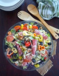 Learn to make this Easy Creamy Italian Salad in about 20 minutes or less for your next last-minute Summer gathering using your favorite ingredients like crisp romaine lettuce, capicola ham, pepperoni, ripe grape tomatoes, garbanzo beans, black olives, green olives, sweet pepper rings, hot pepper rings, grated Romano cheese, and Suddenly Salad.