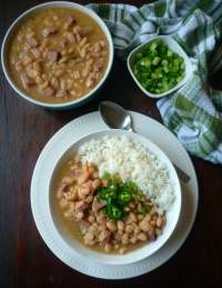 Nothing quite adds a little Southern goodness in your mouth like a big ole pot of slowly simmered Southern-Style White Beans and Ham topped with fresh sliced garden fresh green onions, diced jalapeñopeppers, and served with freshly cooked collard greens and a nice warm buttery slice of cornbread.