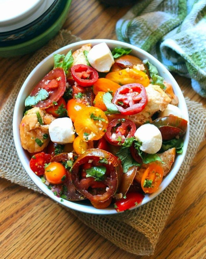 Panzanella With Mozzarella and Herbs is a beautiful Tuscan salad of stale bread and deliciously ripe sweet juicy tomatoes. It is rather simple and to the point, just chunks of soaked stale Italian bread and super juicy ripe organic heirloom tomatoes, fresh mozzarella, red onions, garlic, and fresh herbs, dressed with quality olive oil and red wine vinegar.