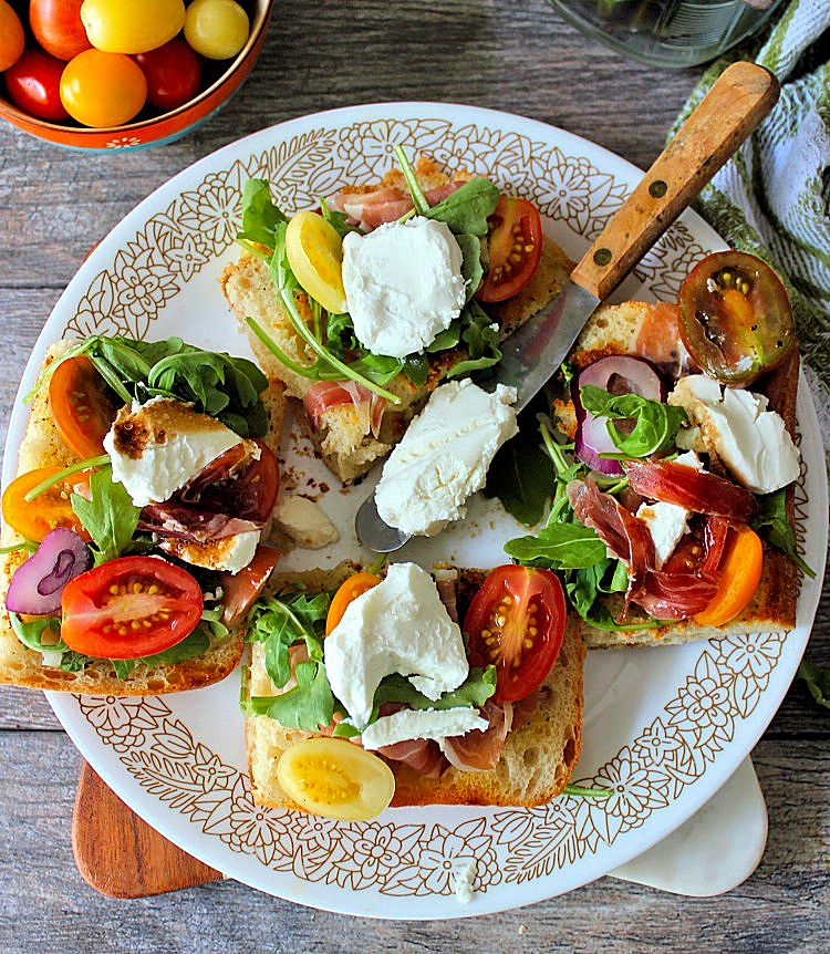Treat your guests to a delicious flavorful lunch of Goat Cheese Tomatoes and Prosciutto on Ciabatta Bread in a snap! How can you go wrong with wonderful flavors like Montchevre Goat Cheese, Heirloom vine-ripened tomatoes, Prosciutto, peppery Arugula, fresh basil, garlic, and warm balsamic? Its a little slice of heaven if you ask me.