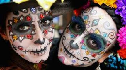 two women painted for Day of the Dead; sugar skulls