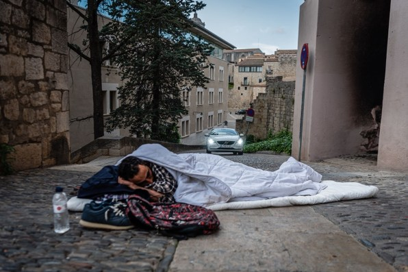 A homeless man sleeps on the street