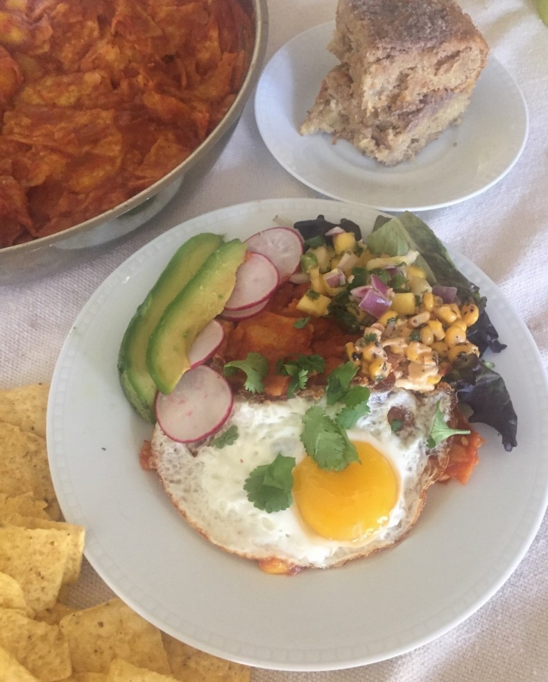 Plate of sweet & smoky chilaquiles, pineapple cinnamon coffeecake in background