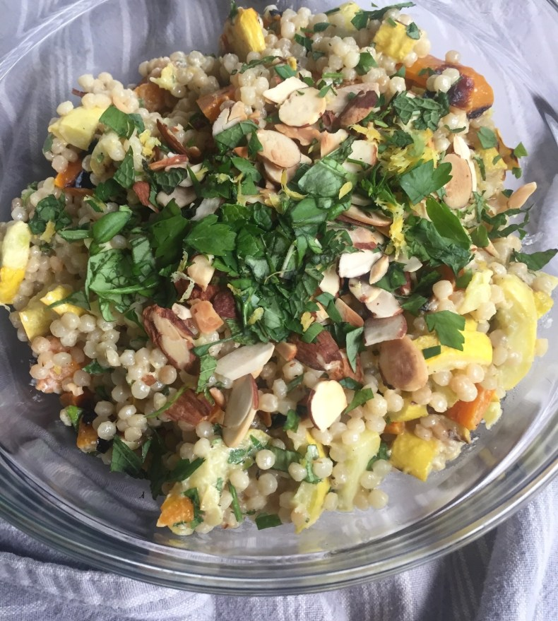 Overhead bowl of Israeli couscous with grilled vegetables and tahini