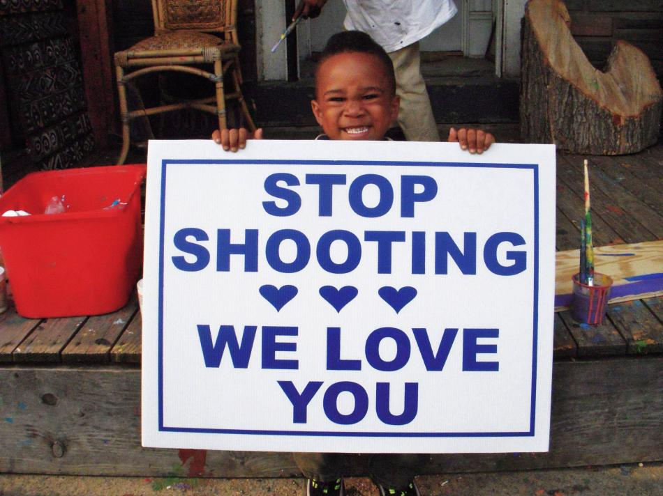 """Stop Shooting, We Love You,"" a child from the Art House holds up the sign."