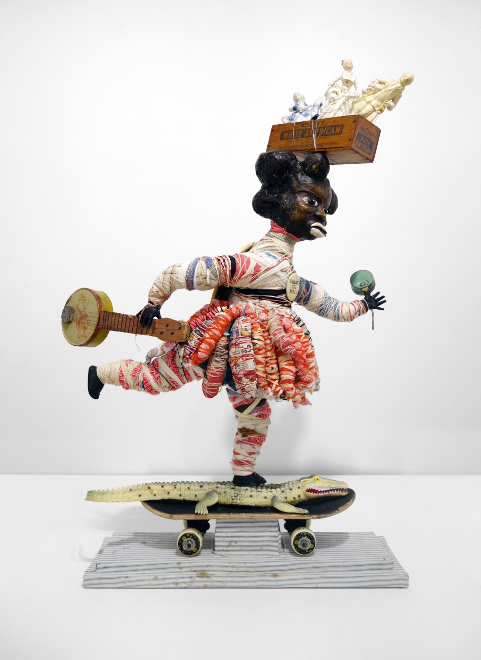 Vanessa German, white american cheese, 2014, skateboard, toy banjo, that-- are we there yet-- feeling, 3 porcelain figures for the White american cheese box, old doll parts, antique blue ticking that is older than i am, tar, red,white, blue, black pigment, cloth, pain, pain, pain, ok ok ok, rhinestone for eyes,i'm not over it, cloth, wood, twine, where's the beef pin, toy alligator, cowrie shells, pressure gauge, mirror on her back-- to watch her back-- who will watch your back--oh lord here we go-- who took my cheese?, 41 x 24 x 10 inches Courtesy of the artist and Pavel Zoubok Gallery, New York