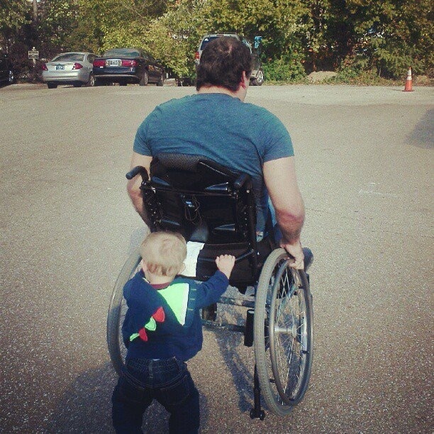 Christine's son pushes his father's wheelchair.