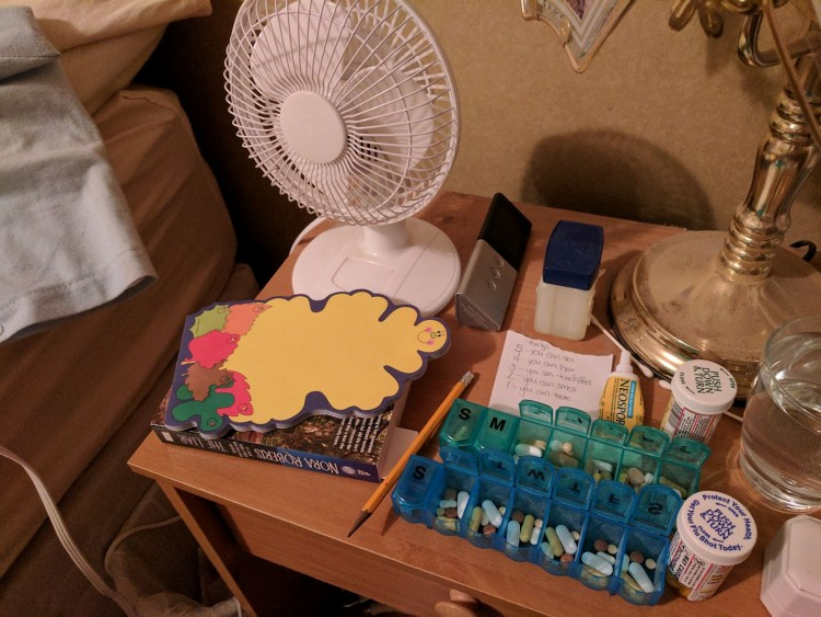 tabla de píldoras, ventilador, libros, bloc de notas