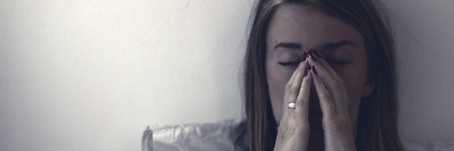 Una mujer sentada en la cama en el dolor.