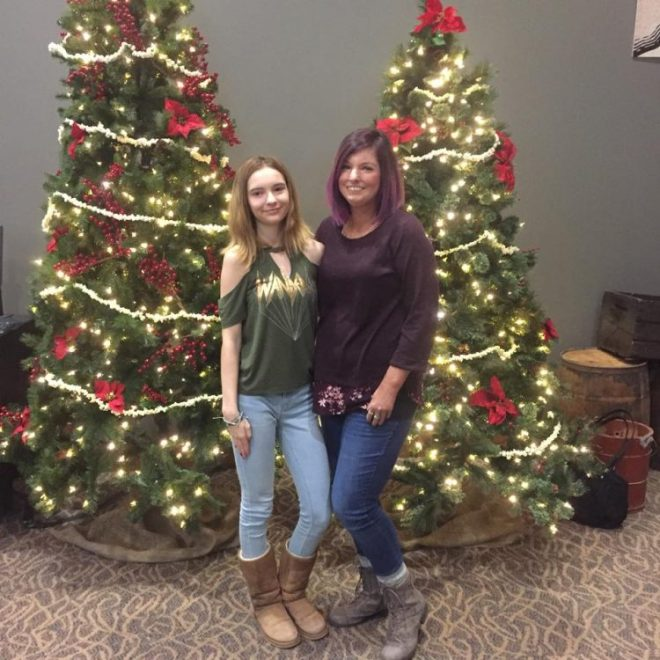 two women standing in front of christmas trees