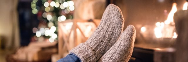 a person wearing socks in front of the fireplace and a christmas tree