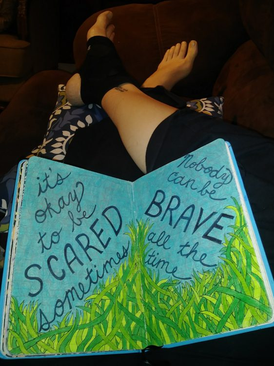 it's ok to be scared sometimes nobody is brave all the time written on paper on woman's legs