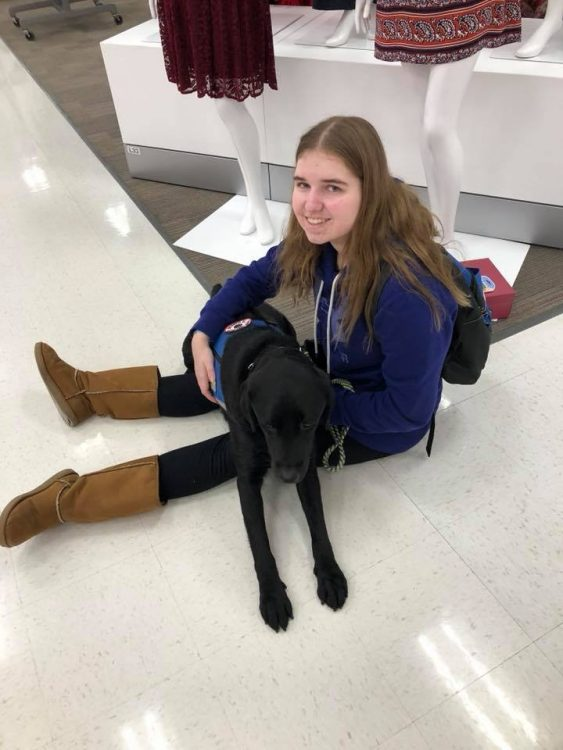 woman sitting on floor of store with service dog