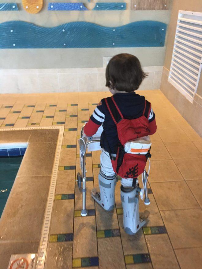 little boy with walker near a pool