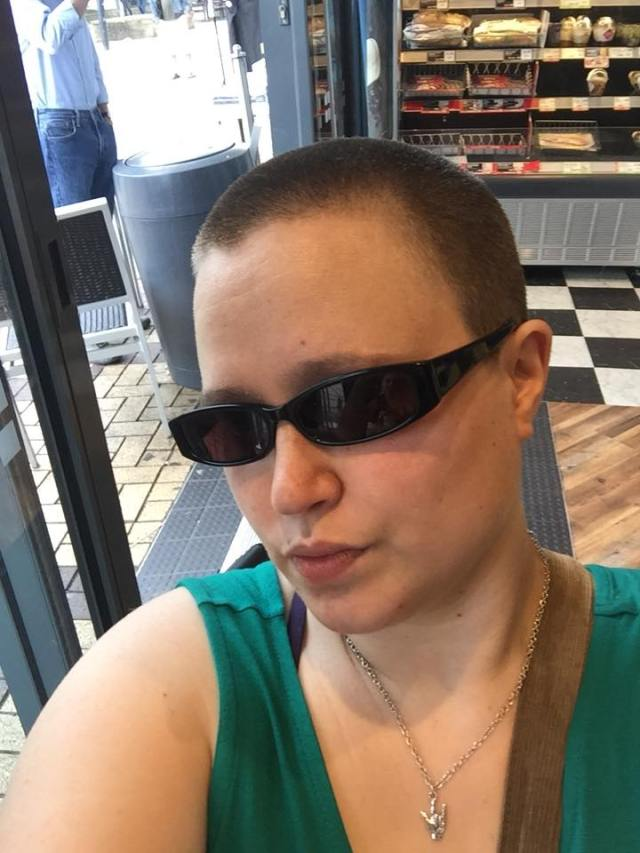a person wearing sunglasses and showing off their shaved head
