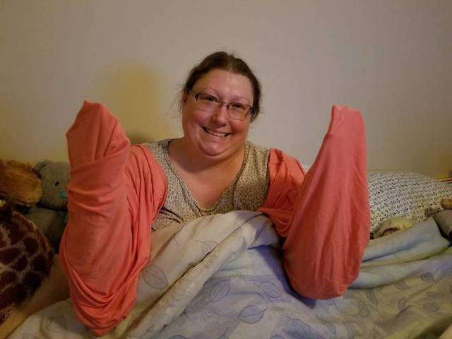 woman with her arms wrapped in soft pink sheets