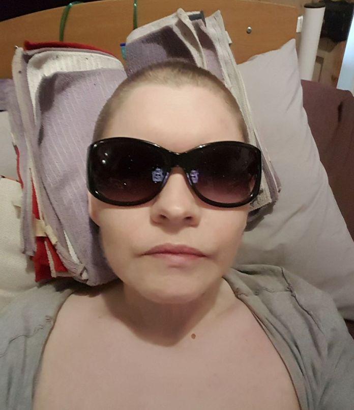 mulher deitada na cama com óculos de sol