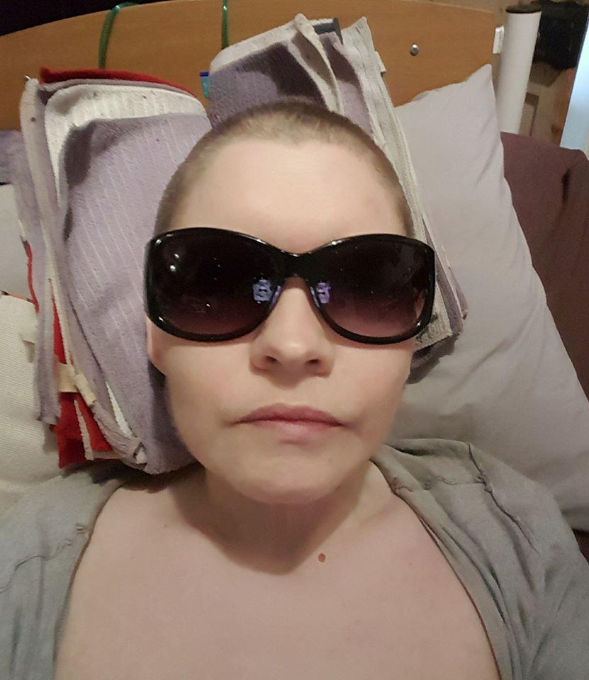femme allongée dans son lit, lunettes de soleil