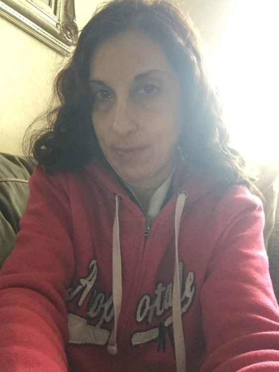 woman wearing a pink hoodie and taking a selfie