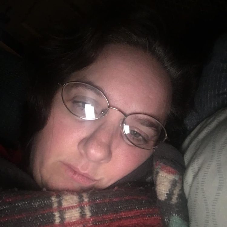 woman lying in bed under a plaid blanket. she's wearing glasses that are slightly askew and her eyes are slightly droopy