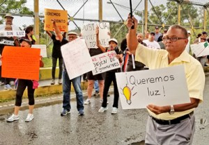 "April 30 protest in Humacao. Second sign from the left says, ""Being old is not a crime. Enough already of the lies and deceit."" The sign next to it reads, ""Lights for everyone, stop ignoring us."""