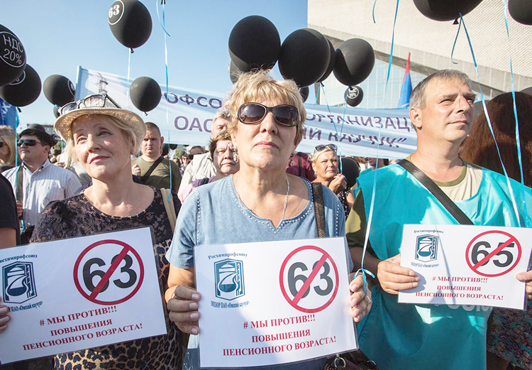 """""""We oppose raising the retirement age,"""" say protest signs in Omsk, Russia. Government proposes to raise age for women from 55 to 63, reflected in signs, and from 60 to 65 for men."""