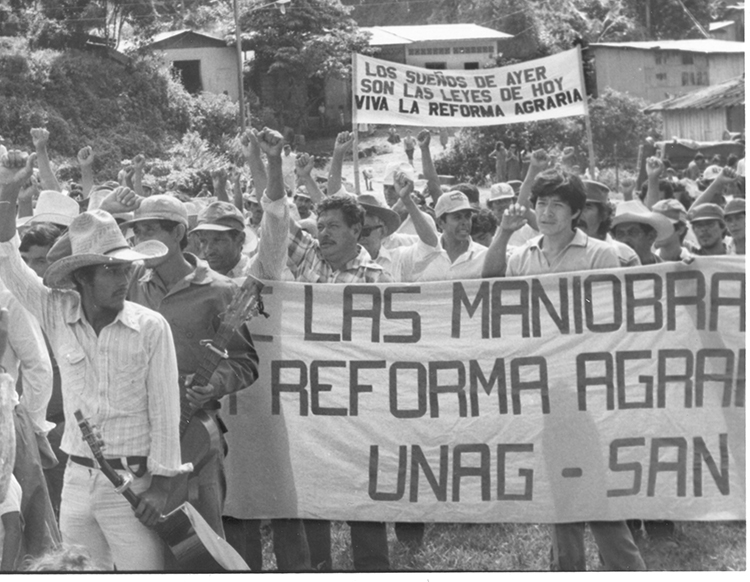 """Peasants celebrate land reform, Santo Tomás, Nicaragua, Dec. 11, 1983. In early years of revolution FSLN responded to peasants fight for land. But over next few years reversed themselves, promising """"patriotic"""" landlords their property would be protected and land reform was dead."""