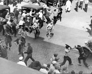 """Arriba, obreros repelen ataque de policía y guardia nacional en mayo de 1934 contra huelga de los Teamsters. En el juicio de dirigentes de los Teamsters y del Partido Socialista de los Trabajadores en 1941, el fiscal le preguntó a James P. Cannon si esta lucha contra los agentes """"es el tipo de violencia promovida por el PST"""". Los agentes """"fueron organizados para expulsar a los trabajadores de las calles. Recibieron una dosis de su propia medicina"""", dijo Cannon. """"Pienso que los trabajadores tienen derecho a defenderse. Si eso es traición, que así sea""""."""