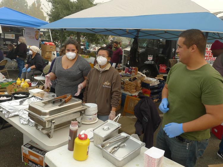 Voluntarios sirven comida a sobrevivientes de incendio en campamento en Walmart, el 15 de nov. Cientos de trabajadores se han ofrecido como voluntarios ante la inacción del gobierno.