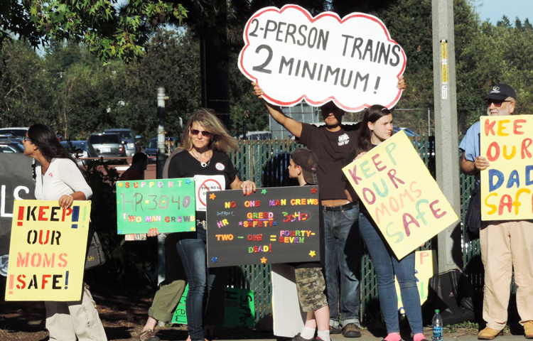 July 2014 protest in Seattle by rail workers and family members against bosses' attempts to slash train crews down to one worker. Bosses seek to increase profits by attacks on workers, farmers and their conditions.