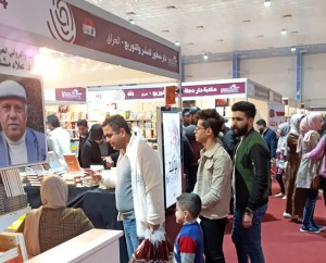 Thousands flocked to International Book Fair in Baghdad in February. At left is photo of Alaa Mashzoub, well-known Iraqi novelist who was murdered just days before start of book fair.