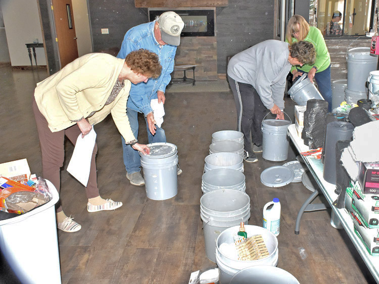 "Volunteers from McCook, Nebraska, organize ""flood buckets"" of supplies to take to areas battered by flooding. Government officials had left those hard hit to fend for themselves."