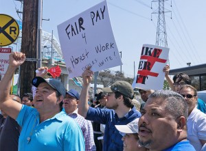 Uber drivers in Redondo Beach, California, March 25, during daylong strike against bosses' 25% per mile pay cut. Union of Uber, Lyft, taxicab and other drivers needed for united struggle.