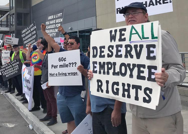 """Como parte de huelga nacional, choferes de Uber y Lyft en Los Angeles apagaron por 24 horas sus aplicaciones y protestaron en el aeropuerto, mayo 8. """"Luchamos por un salario que nos permita vivir"""", dijo el chofer Karim Bayumi. Cartel dice, """"Todos merecemos derechos como empleados""""."""