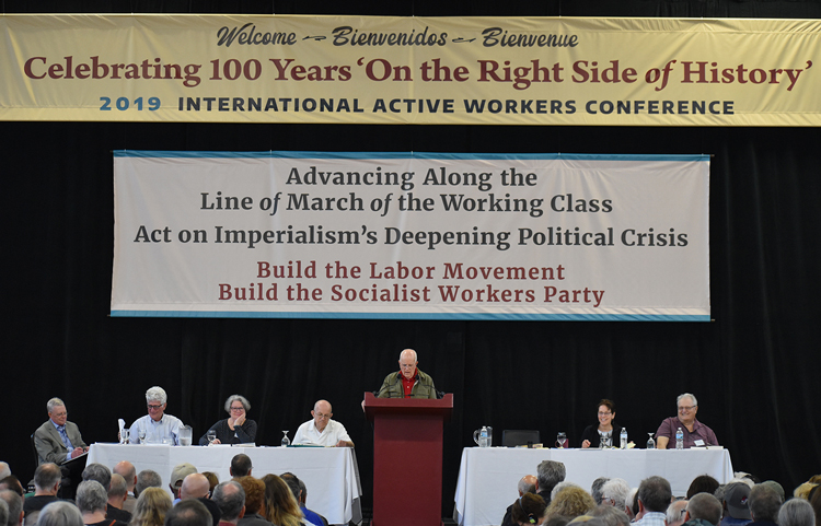 From left, John Studer, Dave Prince, Holly Harkness, Steve Clark, Jack Barnes (speaking), Mary-Alice Waters, Norton Sandler, at closing session of SWP conference June 15. Banners summarized continuity of Socialist Workers Party since 1919 founding of first communist party in U.S. and other Active Workers Conference themes.