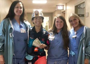 """Chinese restaurant owner Joyce Cheng, in miner's helmet and jacket, with nurses at Harlan Appalachian Regional Healthcare July 11. She ran 50 miles """"asking every person for a dollar"""" for laid-off Blackjewel miners, raising over $5,000 for miners' families she knows."""