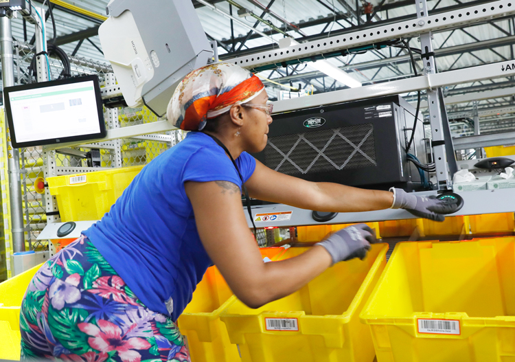 Worker at Amazon Fulfillment Center in Staten Island, New York, hits button to indicate order robotically transported to her workstation is done. Bosses' speedup has led to increase in on-the-job injuries. Inset, company tests drone making deliveries.