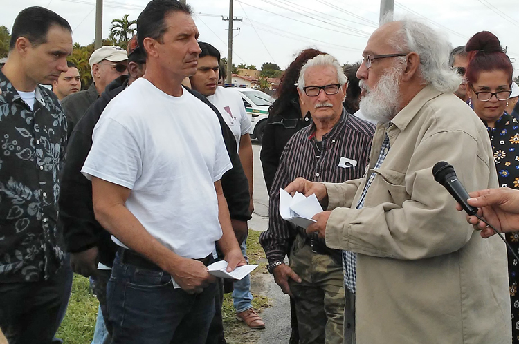 Andrés Gómez, right, leader of Alianza Martiana, speaks before 50-car caravan wound its way through Miami's Little Havana Feb. 8, calling for end to new U.S. attacks on travel to Cuba.