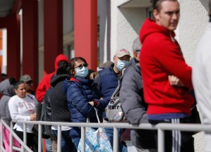Workers, suddenly without jobs, line up for unemployment benefits in Las Vegas March 17. The virus outbreak triggered the coming depression, which has been looming for some time.
