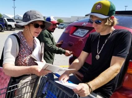 Garrett Bell picks up copy of Militant from Alyson Kennedy at Dallas area Walmart parking lot.