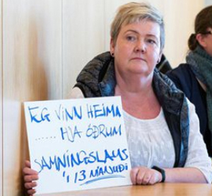 "Solveig Anna Jonsdottir, chair of Efling Union and a cleaner, holds sign at May 5 union meeting: ""I work at home ... other people's homes, without a contract for 13 months."""
