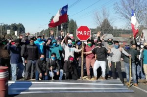 """Road blocked by some of 500 workers in 43-day strike at Promasa, a lumber company in Los Ángeles, Chile, one of number of recent strikes and protests. Mass anti-government protests that began in October """"are going to explode again soon,"""" union leader at Holdtech strike predicted."""