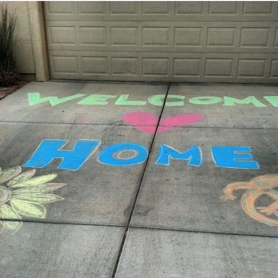 welcome home written on driveway with chalk