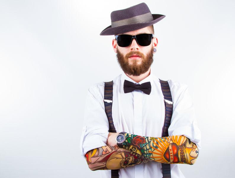 un giovane hipster con bretelle, barba e cappello anni 40