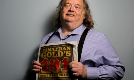 LA Times food critic Jonathan Gold holds up a newspaper featuring his top 101 restaurants in LA.