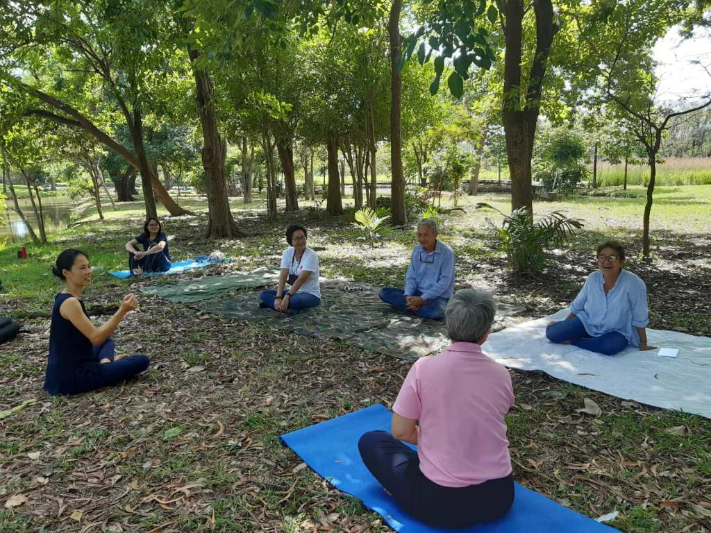 Forest Bathing Certification Training with a group of persons listening to a speaker in the forest